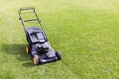 stock photo of grass-cutter  - lawn mower on green grass lawn in sunny day - JPG
