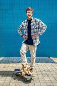 foto of skateboard  - Skateboarder smiling with a toy bear on the board in city on skateboard at the background wall tiles - JPG