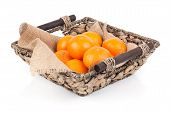 picture of clementine-orange  - A wicker basket full of fresh orange fruits isolated on a white background - JPG