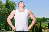 stock photo of breath taking  - Portrait of a young handsome muscular sportsman taking a deep breath relaxing after a hard training in a park - JPG