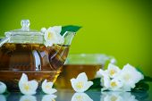 picture of jasmine  - jasmine tea in a teapot with a branch of jasmine on a green background - JPG