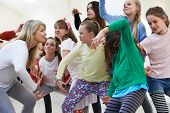 stock photo of 11 year old  - Group Of Children With Teacher Enjoying Drama Class Together - JPG