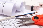 stock photo of electrical engineering  - Cable cutter electric wire and fuse rolls of electrical diagrams lying on construction drawing of house accessories for engineer jobs - JPG