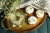 stock photo of chamomile  - Cup of chamomile tea with chamomile flowers and tasty muffins on tray - JPG