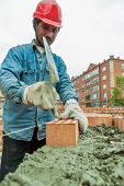foto of trowel  - Tyumen, Russia - May 23, 2008: 18 floor residental house at intersection of streets of Gercena and Chelyuskincev. Construction mason worker bricklayer installing red brick with trowel putty knife
