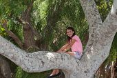 picture of preteen  - Preteen girl happily sits on a tree branch - JPG