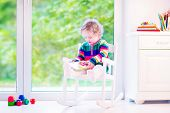 picture of daycare  - Cute curly little girl funny toddler wearing a warm colorful knitted dress reading a book relaxing in a white rocking chair next to a big garden view window at home or daycare center - JPG