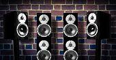 pic of speaker  - Black high gloss music speakers on brick wall - JPG