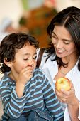 pic of grocery-shopping  - Woman and son at a supermarket eating fruits - JPG