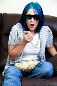 stock photo of beautiful woman  - Beautiful young woman watching a 3d dvd movie on tv at home with popcorn - JPG