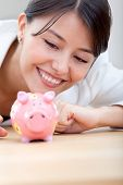 Business woman looking at a a piggybank and smiling