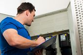 stock photo of electricity meter  - Technician reading the electricity meter to check consumption - JPG