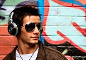 Sexy Image of a Male DJ wearing headphones and aviator sunglasses stood in front of graffiti