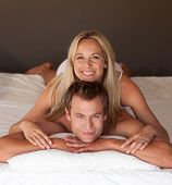 stock photo of woman couple  - Beautiful woman on a mans back in bed having fun - JPG