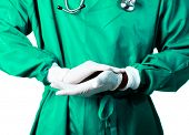 image of medical supplies  - Senior Surgeon putting on his gloves before surgery - JPG