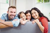 Portrait of happy family leaning on sofa at home poster