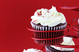 foto of red velvet cake  - Red velvet cupcake in a red cupcake holder against a red background with copy space included - JPG