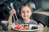 Little Cute Little Girl Eating Sushi In A Cafe, Concept Of Eating poster