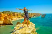 Tourism In Algarve. Freedom Lifestyle Tourist On Promontory Above Scenic Praia Da Marinha. Caucasian poster