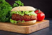 Fresh Vegan Burger With Tomato, Cucumber, Lettuce And Vegan Cutlet On Wooden Board. poster