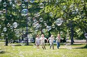 Green Public Park Illuminated With Sunbeams, Colorful Soap Bubbles Flying In Air, Group Of Little Ch poster