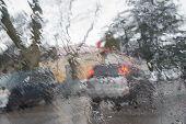 Rain Drops On Car Glass. Rainy Weather, Evening. Rain Drops On Window, Rainy Weather. Blurry Car Sil poster