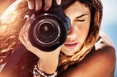 Closeup portrait of a beautiful girl with camera on the beach, cute young photographer taking pictur poster