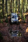 Dirty Offroad Car With Fall Forest On Background. Suv Covered With Mud On Path Covered With Leaves.  poster