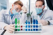 Selective Focus Of Scientific Researchers In Goggles And Medical Masks Looking At Reagents In Tubes  poster