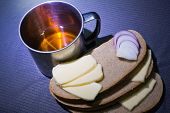 stock photo of scant  - steel cup with tea bread cheese and onion - JPG