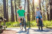 Happy attractive couple on a bike ride together outdoors on a bicycle path in the woods. Bike rental poster