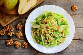 Постер, плакат: Easy Pear And Cabbage Salad Home Salad With Fresh Raw Pear Cabbage And Walnuts On A White Plate An