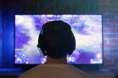 Постер, плакат: Gamer Or Streamer In Earphones With Microphone Sits At Home In Dark Room And Plays With Friends On N