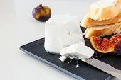 Goat Cheese, Fresh Ripe Fruit Figs And Freshly Baked French Baguette. Light Background. poster