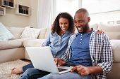 Young black couple using laptop sitting on the floor at home poster