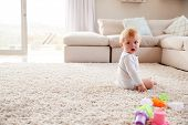 White toddler boy sitting on the floor in sitting room poster