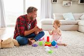 Young father and toddler daughter clapping in sitting room poster