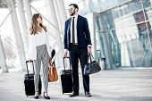 Business Couple Walking With Luggage Near The Airport During The Business Trip poster