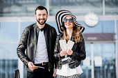 Portrait Of A Young Couple In Leather Jackets Standing With Tickets And Luggage Near The Airport Dur poster