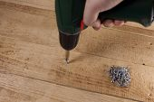 Screw Screwed With Drill Into Wooden Board. Close-up poster