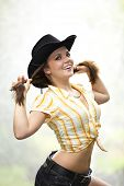 pic of waterspout  - A smiling beautiful brunette woman with a cowboy hat in her twenties tearing her hair - JPG
