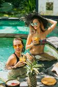Attractive Young Women In Swimwear Drinking Tropical Cocktails And Resting Together In Pool poster