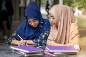 Teenager Young Adult Asian Thai Muslim university college students reading book and using digital ta poster
