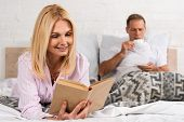 Smiling Woman Reading Book While Husband Drinking Coffee In Bed poster