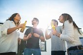 Relaxed Carefree Friends Enjoying Party And Drinking Beer On Outdoor Terrace. Young Men And Women In poster