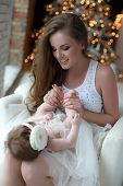 Happy mother holding a small child in her arms opposite the Christmas tree.New Year.christmas and fa poster