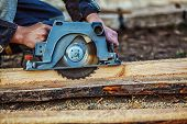 Circular Saw For Cutting Boards Into The Hands Of The Builder, The Man Sawed Bars, Construction And  poster