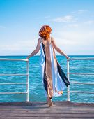 Behind Girl On Pier. Woman In Colorfull Dress Standing On The Pier. poster