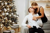 Couple In Love Kisses And Hugs On The Sofa Near The Christmas Tree Lights. New Years Night.christmas poster