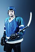 Portrait of a handsome ice-hockey player with hockey stick. Studio shot.